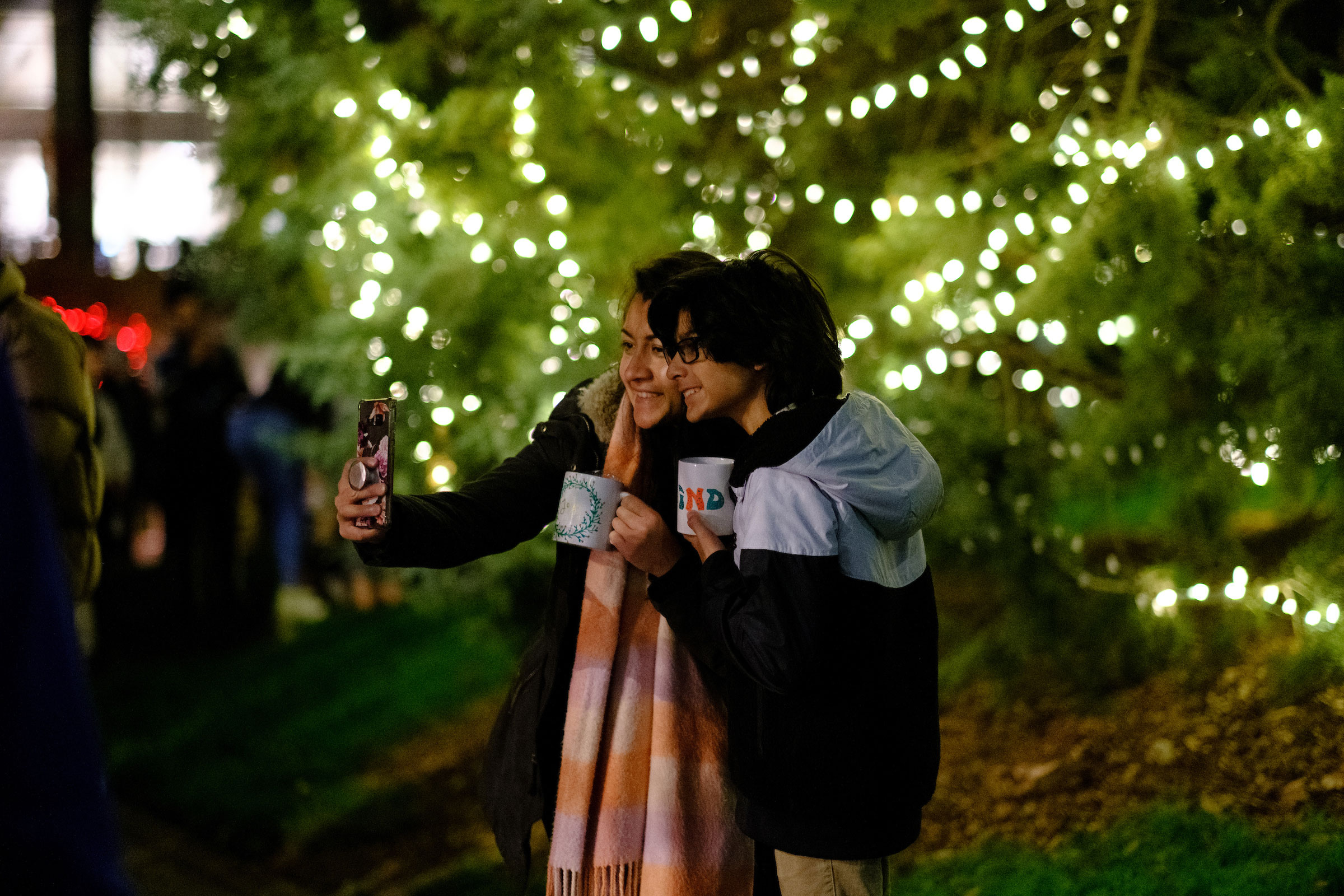 two students pose for a group selfie in front of the campus Christmas Tree