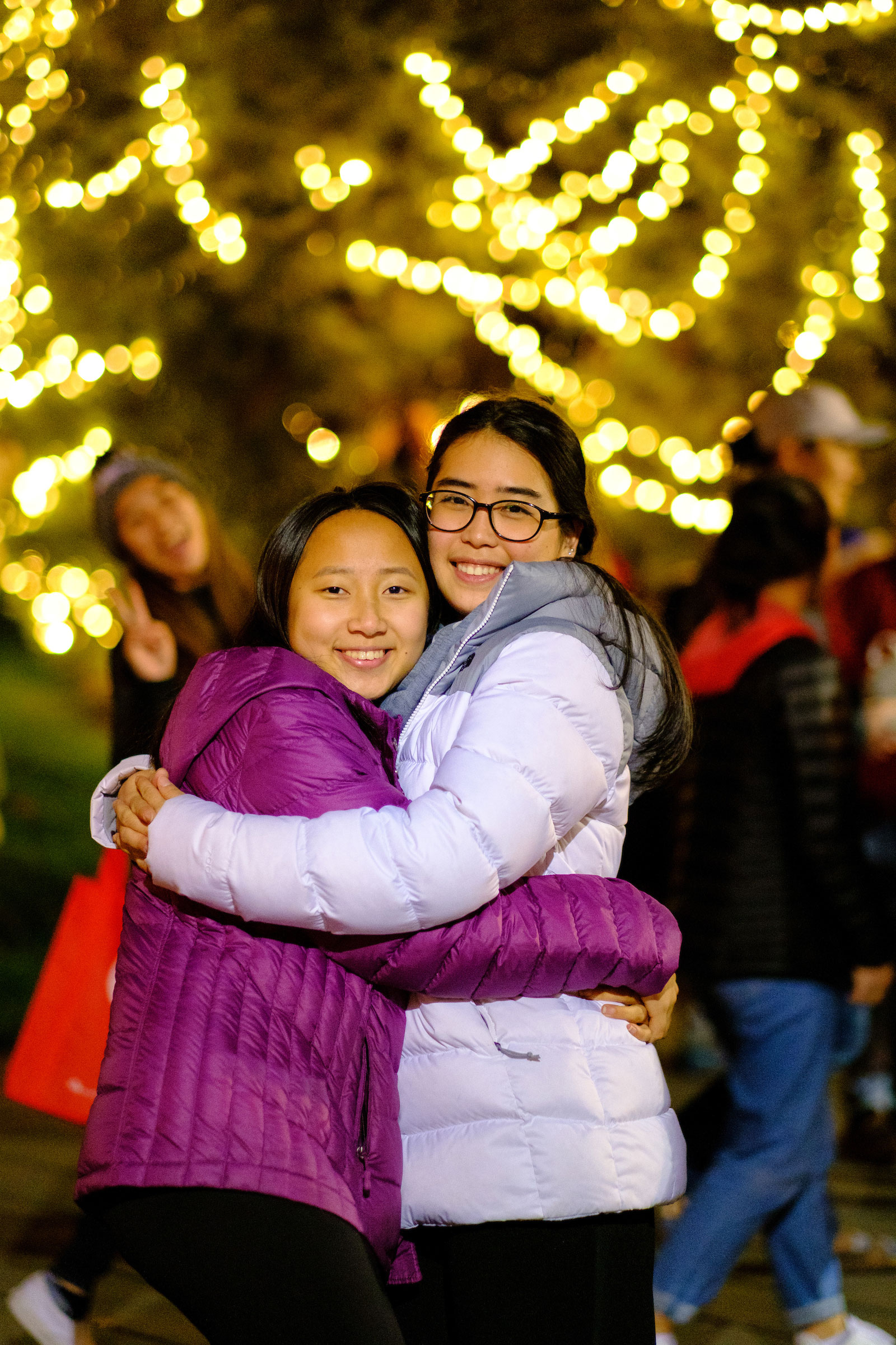 two students hugging in front of the campus Christmas Tree