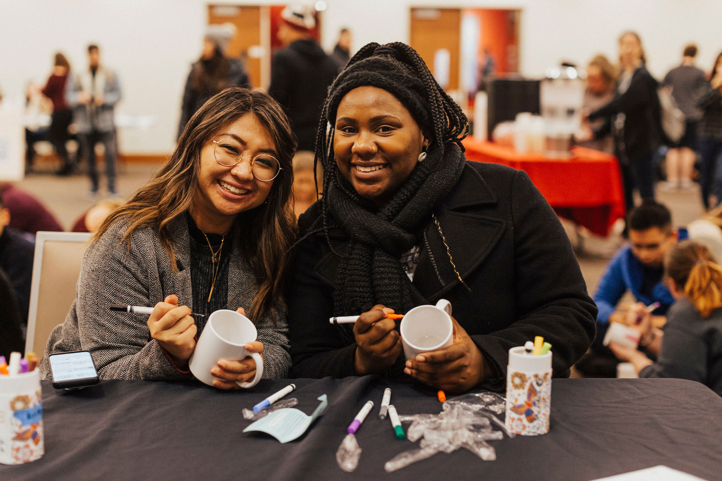 two students pose for a shot while decorating mugs