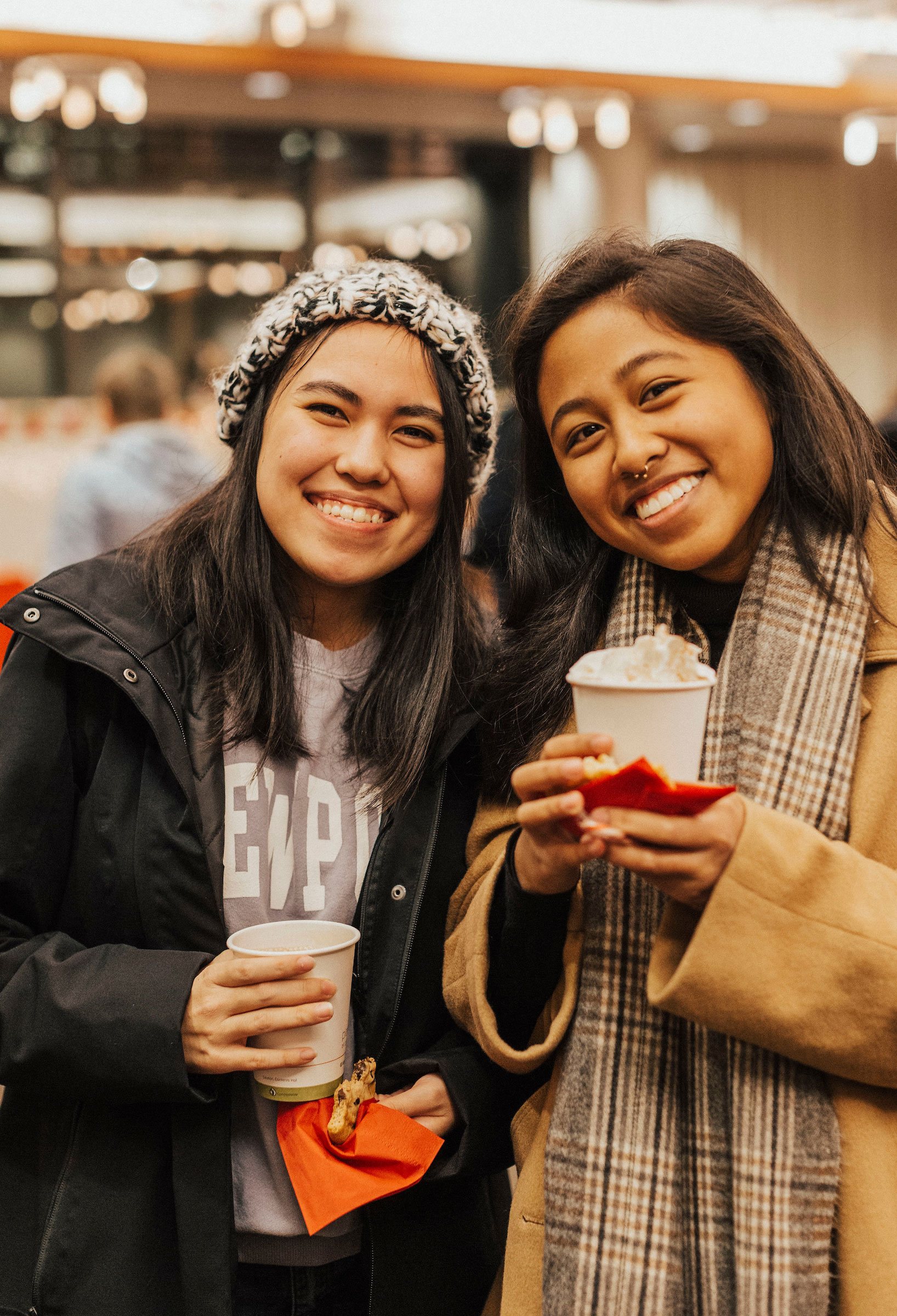 two students smile holding warm festive beverages