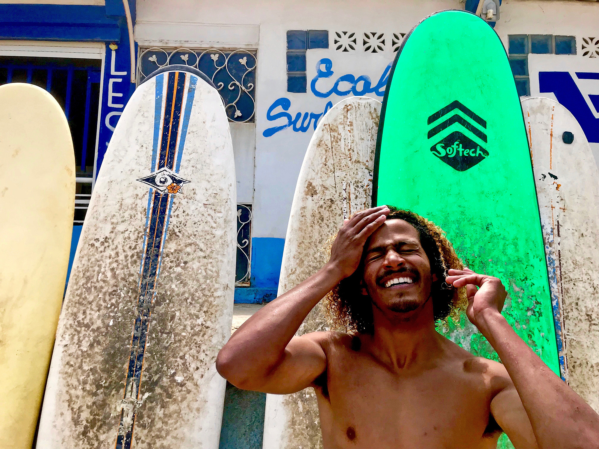 a shirtless man smiles in front of several surfboards leaning against a tiled wall