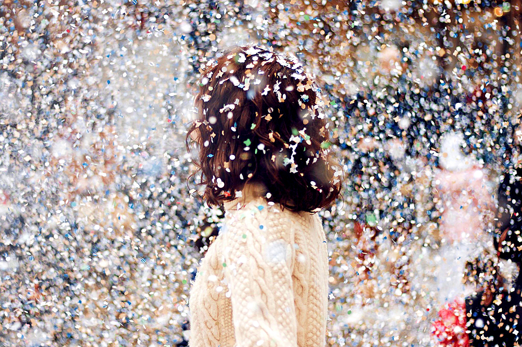 a woman with long brown hair stands amidst a flurry of multi-colored confetti