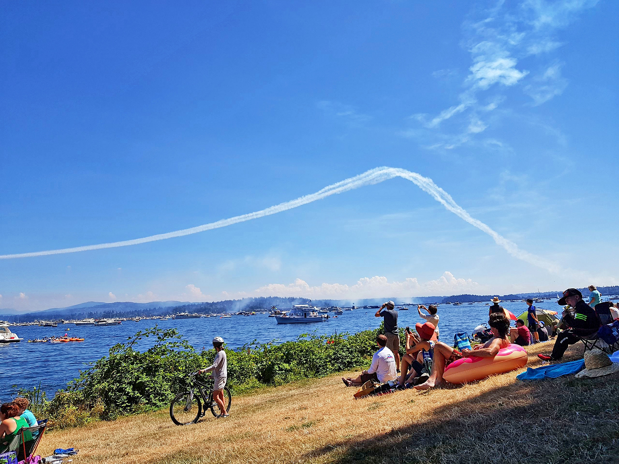 Seafair attendees at Lake Washington scan a blue sky filled with contrails for the Blue Angels
