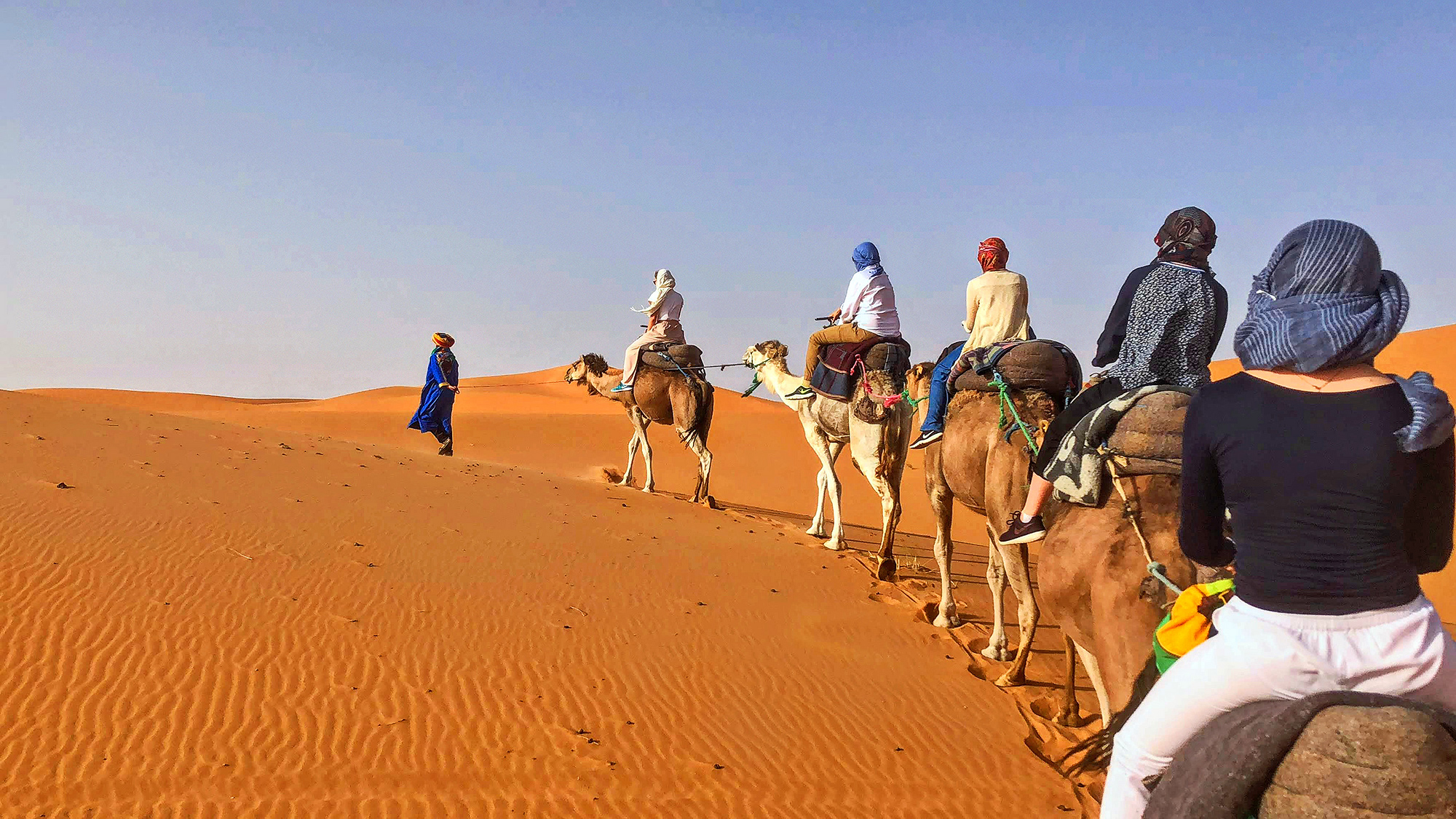 caravan of travelers riding camels in the Moroccan desert