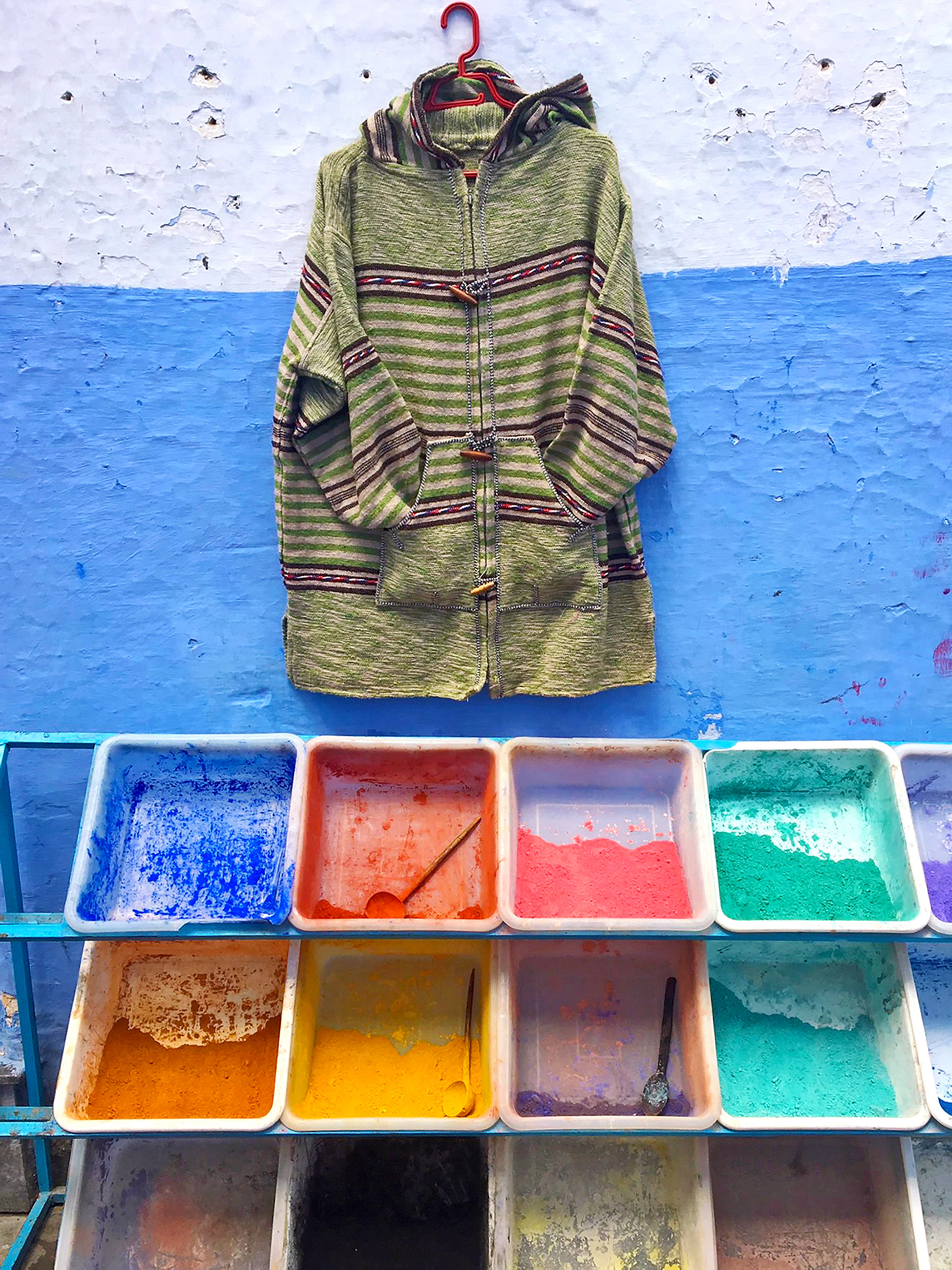 a zippered hooded jacket hangs on a wall painted white and blue above open bins of colored pigment