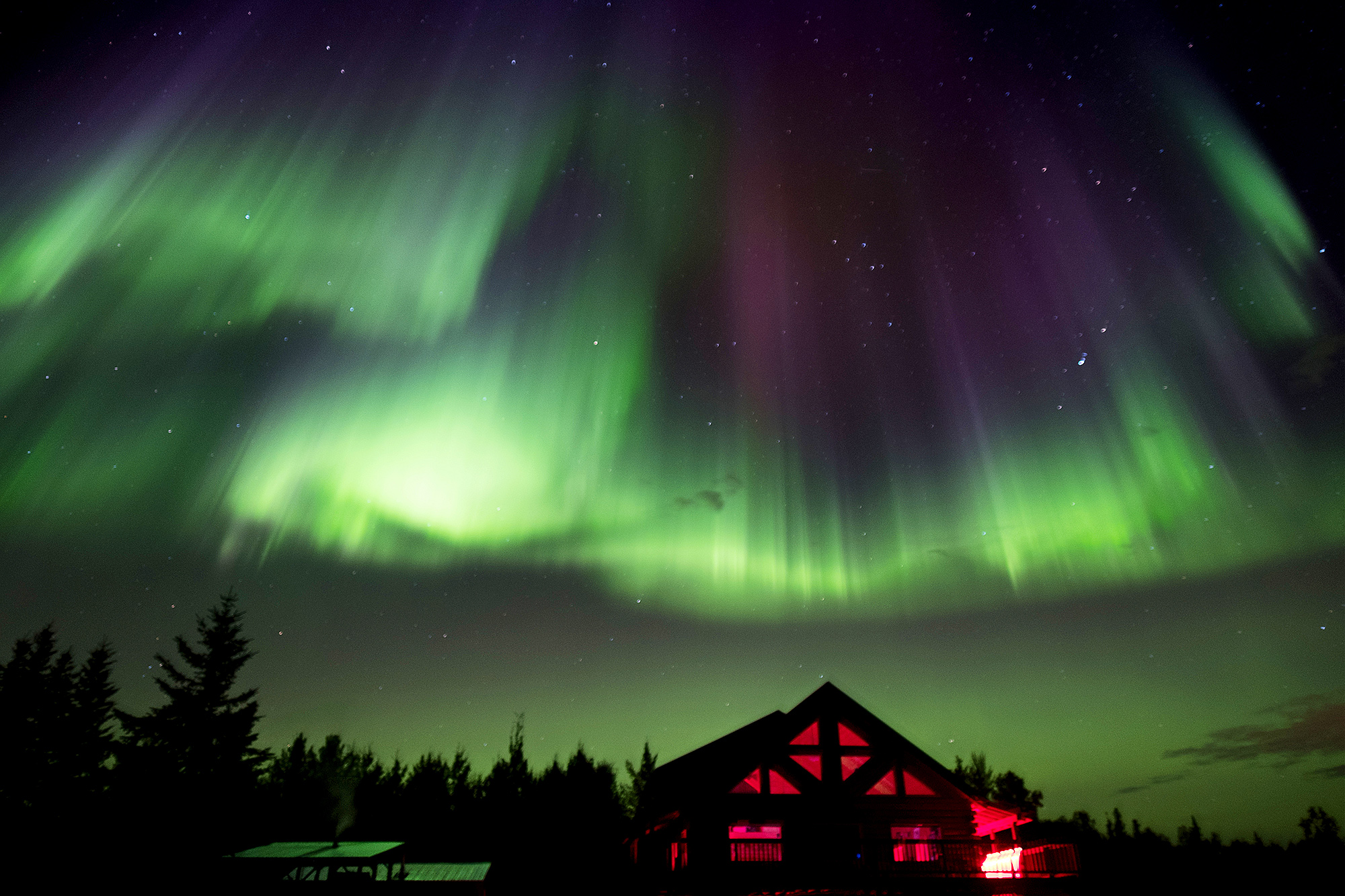 a cabin glows a warm red beneath the green and purple Aurora Borealis lights in a starry night sky