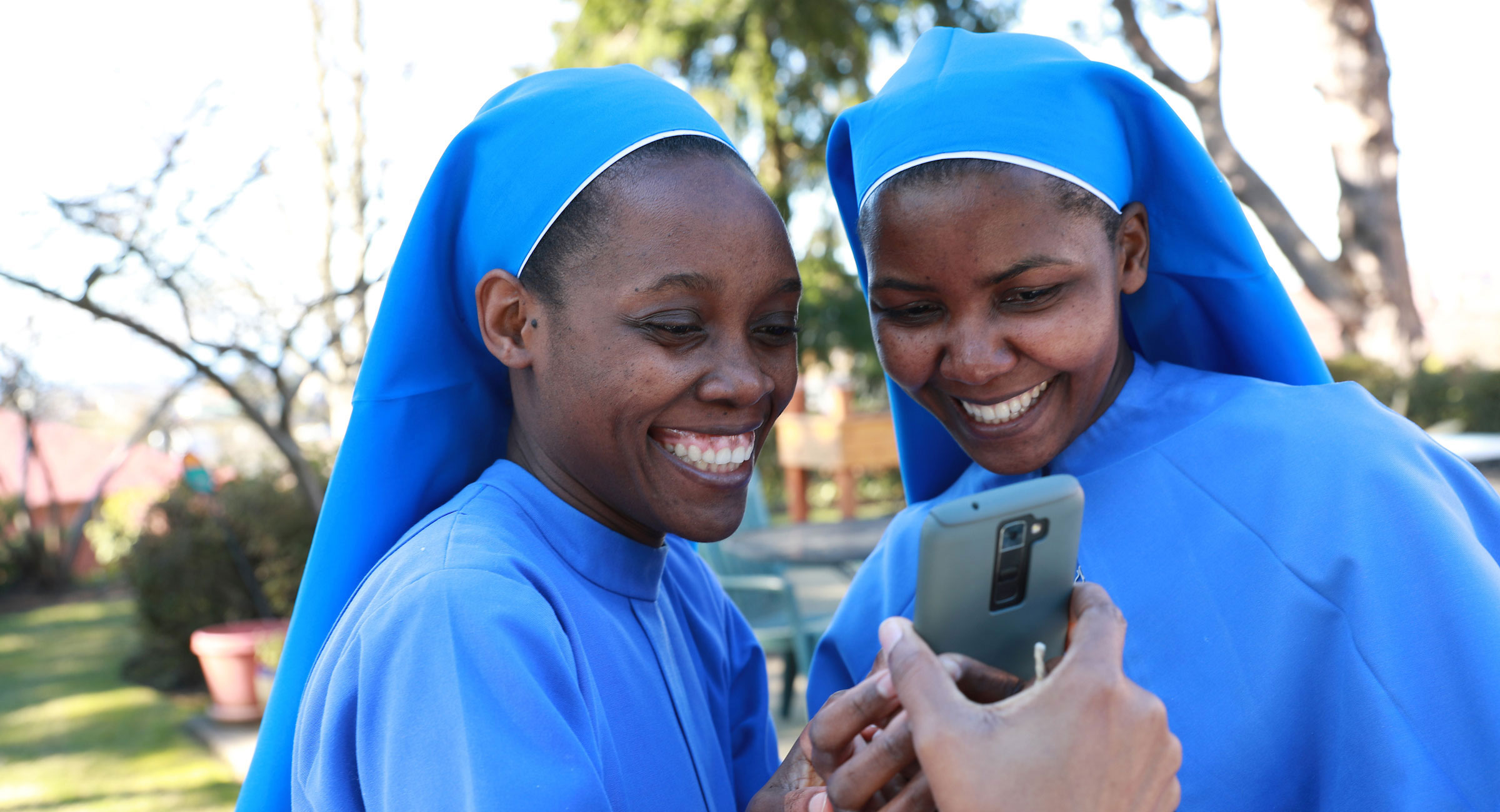 Sister Mary Namutebi, DM, '20, '22, left and Sister Paskazia Ampronia Nakitende, DM, '19 with The Daughters of Mary Sisters in Uganda share a moment together while reviewing a selfie photo they took on their cell phone in the garden at their St. Joseph's Residence in West Seattle.