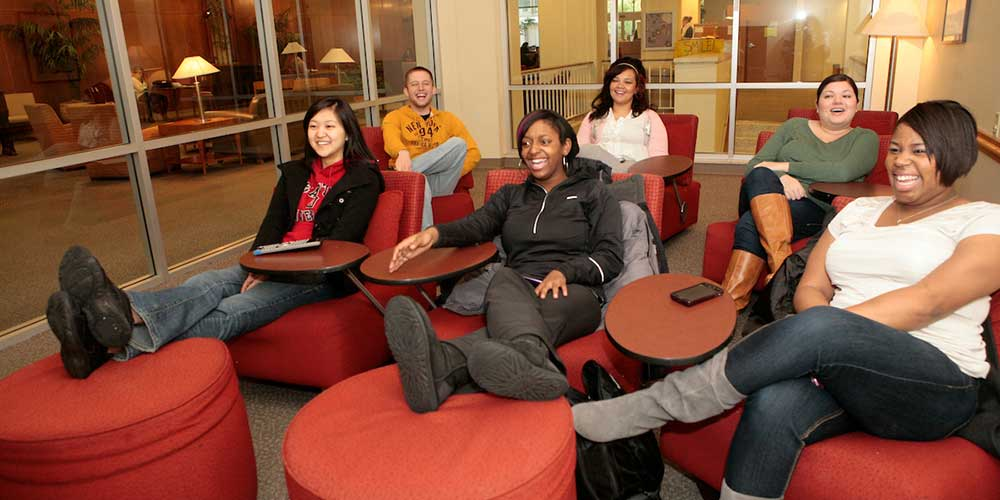 Six students sit in a dorm lounge